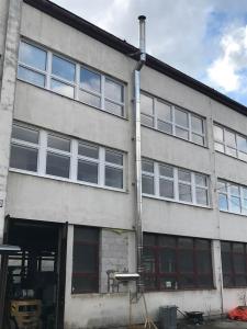 Trojvrstvový nerezový komín vedený po fasáde budovy.